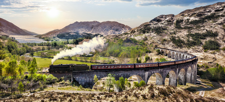 vintage landscape: Glenfinnan Railway Viaduct in Scotland with the Jacobite steam train against sunset over lake
