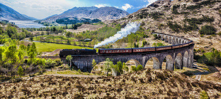 the jacobite: Glenfinnan Railway Viaduct in Scotland with the Jacobite steam train against sunset over lake