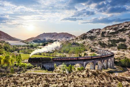 グレンフィナン湖に沈む夕日に対してジャコバイト蒸気機関車列車とスコットランドの鉄道高架橋