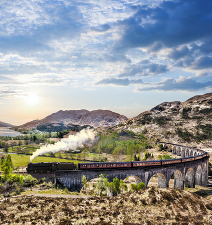 highland: Glenfinnan Railway Viaduct in Scotland with the Jacobite steam train against sunset over lake