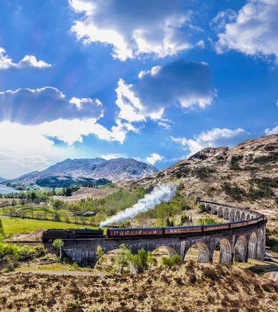 railroads: Glenfinnan Railway Viaduct in Scotland with the Jacobite steam train against sunset over lake