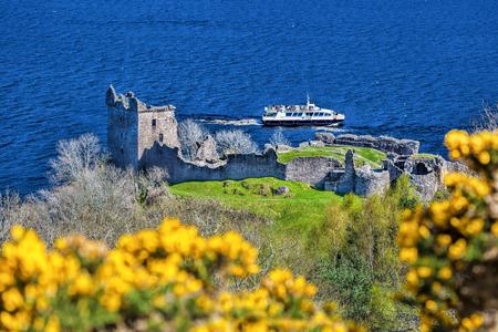Ruins of Urquhart Castle against boat on Loch Ness in Scotland Foto de archivo