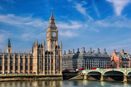 Big Ben with three double deckers buses on the bridge in London, England Stock Photo