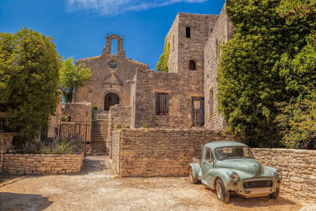 alley: Village of Saignon with old car against church in the Luberon, Provence, France Stock Photo