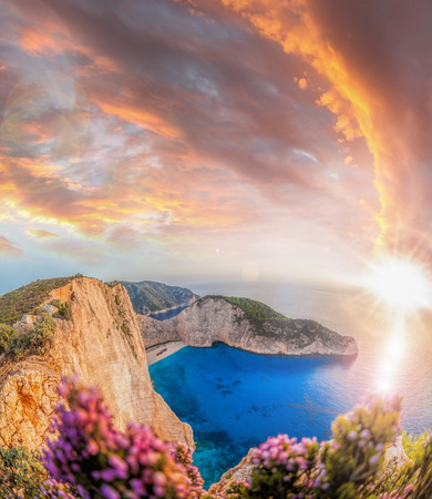 sunrise ocean: Navagio beach with shipwreck and flowers against sunset on Zakynthos island in Greece