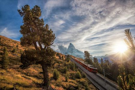 Matterhorn peak with a train against sunset in Swiss Alps, Switzerland
