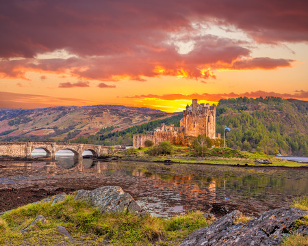 highland: Eilean Donan Castle against sunset in Highlands of Scotland