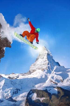 Snowboarder jumping against Matterhorn peak in Switzerland photo