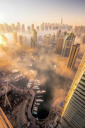 highest: Dubai Marina is covered by early morning fog in Dubai, United Arab Emirates