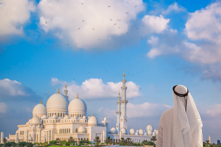 abudhabi: Arabian man watching Sheikh Zayed Grand Mosque in Abu-Dhabi, United Arab Emirates Stock Photo