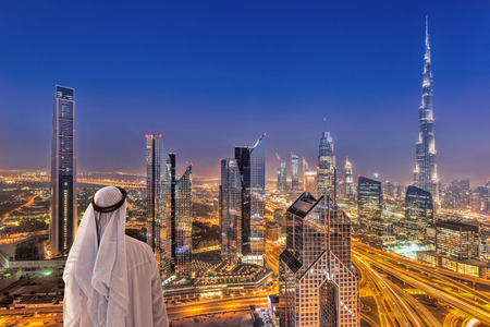 Arabian man watching night cityscape of Dubai with modern futuristic architecture in United Arab Emirates 版權商用圖片