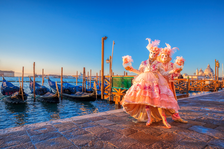 Famous carnival masks against gondolas in Venice, Italy Stock Photo