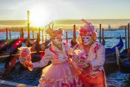 Famous carnival masks against gondolas in Venice, Italy Stock Photo