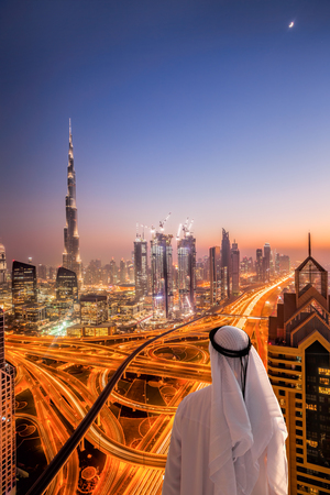 Arabian man watching night cityscape of Dubai with modern futuristic architecture in United Arab Emirates Banco de Imagens