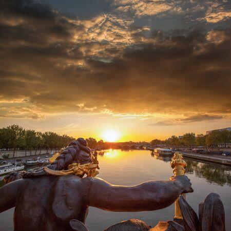 Alexandre III bridge against colorful sunset in Paris, France