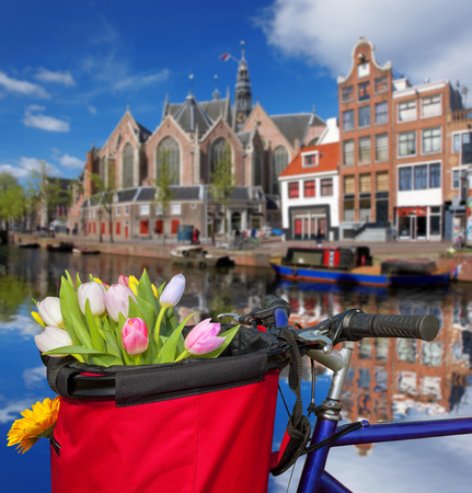 Famous Amsterdam with basket of colorful tulips against canal in Holland Stock Photo