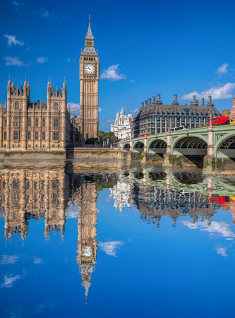 London with red buses against Big Ben in England, UK Editorial