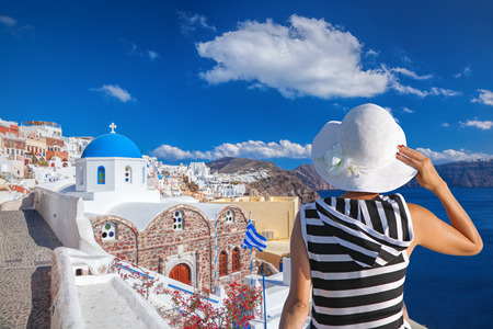 cycladic: Woman with hat watching Oia village on santorini island in Greece
