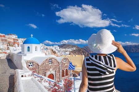 fira: Woman with hat watching Oia village on santorini island in Greece