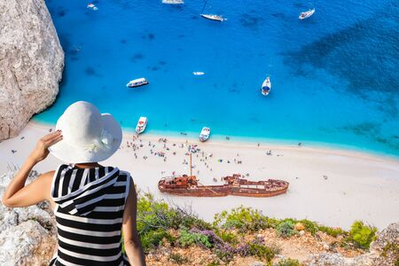 Woman with hat watching Navagio beach with shipwreck on Zakynthos island in Greece Stock Photo