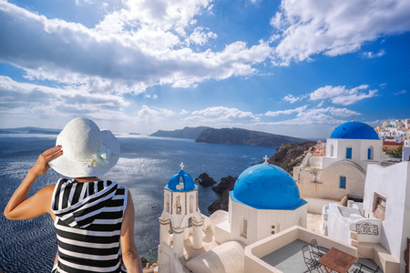 religious clothing: Woman with hat watching Oia village on santorini island in Greece