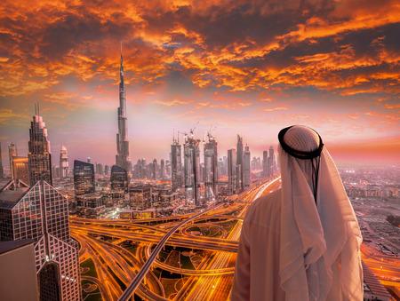 Arabische mens die op cityscape van Doubai met moderne futuristische architectuur in Verenigde Arabische Emiraten letten. Stockfoto