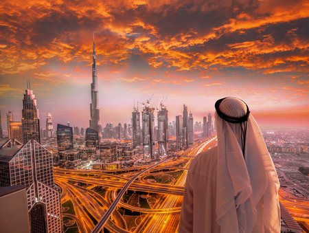Arabian man watching cityscape of Dubai with modern futuristic architecture in United Arab Emirates. Banque d'images