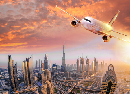 Airplane is flying over Dubai against colorful sunset in United Arab Emirates 스톡 콘텐츠