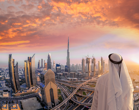 Arabian man watching cityscape of Dubai with modern futuristic architecture in United Arab Emirates. Stock Photo