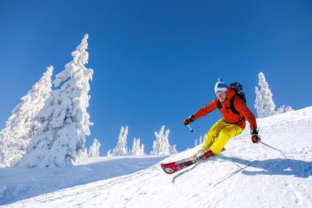 青い空に対して高い山の中でスキーヤーのスキー下り坂