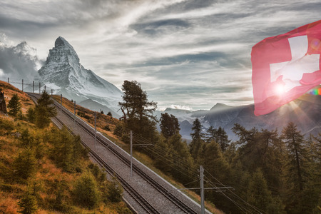 Matterhorn peak with railway against sunset in Swiss Alps, Switzerland