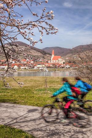 Cyclists against Weissenkirchen village in Wachau during spring time, Austria