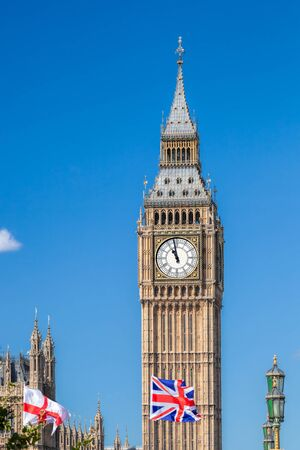 Big Ben with flags of England in London, UK