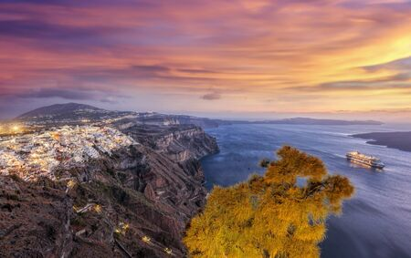 Old Town Thira on the Santorini island, famous churches against colorful sunset in Greece