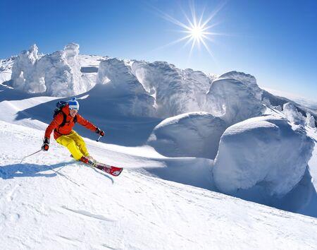 Skifahrer Skifahren bergab in hohen Bergen gegen blauen Himmel Standard-Bild