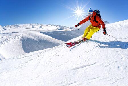 Skiër skiën bergafwaarts in hoge bergen tegen blauwe hemel