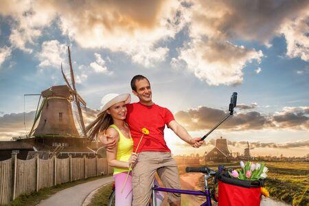 Happy couple on bike against traditional Dutch windmills in Zaanse Schans, Amsterdam area, Holland