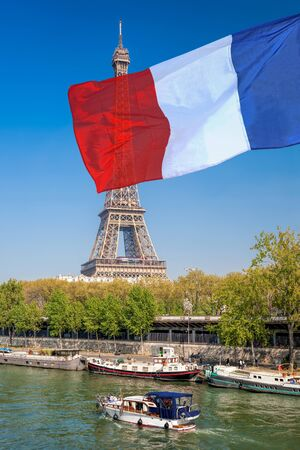 Paris with Eiffel Tower against french flag during spring time in France