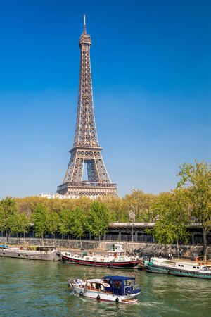 Paris with Eiffel Tower against boats during spring time in France