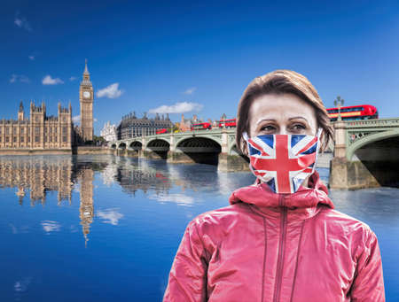 Woman wearing protection face mask with British flag against coronavirus in front of Big Ben, London, England