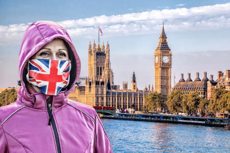 Woman wearing protection face mask with British flag against coronavirus in front the of Big Ben, London, England