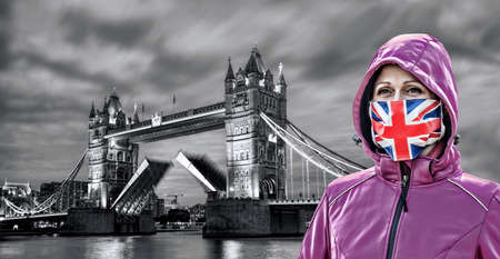 Woman wearing protection face mask with British flag against coronavirus in front of the Tower Bridge, London, England 免版税图像