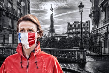 Woman wearing protection face mask with French flag against coronavirus in front of the Eiffel Tower in Paris, France 免版税图像