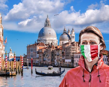 Woman wearing protection face mask with Italian flag against coronavirus on Grand canal in Venice, Italy Standard-Bild