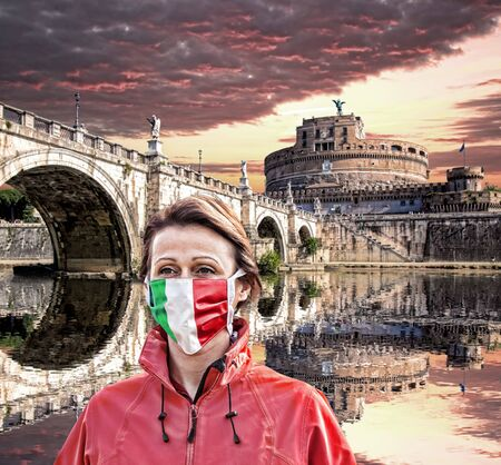 Woman wearing protection face mask with Italian flag against coronavirus in front of the Angel Castle with bridge, Rome, Italy