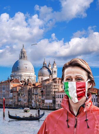 Woman wearing protection face mask with Italian flag against coronavirus on Grand canal in Venice, Italy