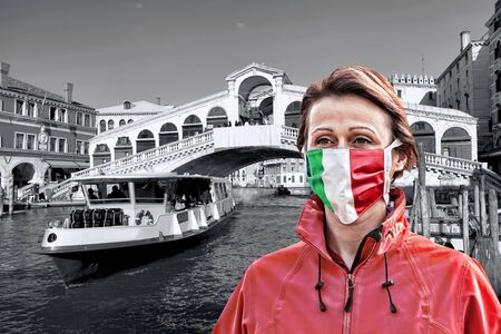 Woman wearing protection face mask with Italian flag against coronavirus in front of the Rialto bridge, Venice, Italy Zdjęcie Seryjne
