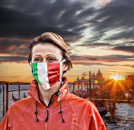 Woman wearing protection face mask with Italian flag against coronavirus in Venice, Italy
