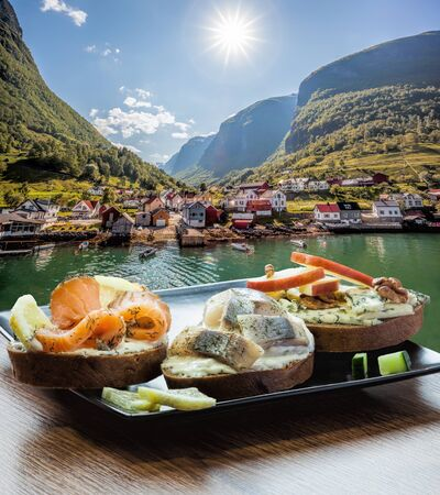 Typical Scandinavian sandwiches against typical fishing village with fjord in Norway near Flam
