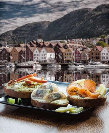 Typical Scandinavian sandwiches against Bryggen street with boats in Bergen